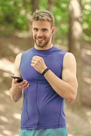 Set up application. Sportsman with smartphone and smart watch prepare for jog. Training with sport application is more fun. Set up route for run using application. Man smartphone ready to start jog
