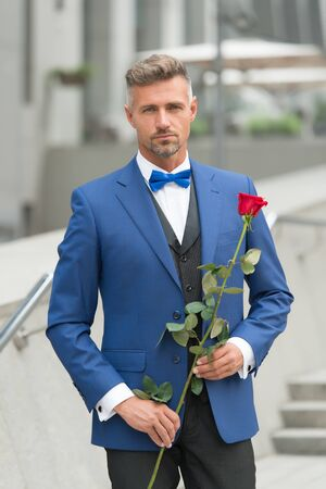 handsome boyfriend holding red rose. businessman hold red rose. elegant and confident man. groom in classic jacket. charismatic man wear wedding suit. Theatre and Opera. going in restaurant on date