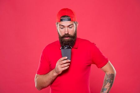 Amazing coffee. best quality of cafe service. good morning coffee to go. bearded man drink tea red background. brutal hipster in uniform. surprised barista hold coffee cup. take away coffee here