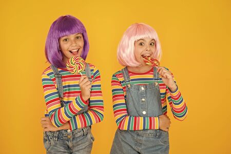 Kids with artificial hairstyles eating lollipops. Anime convention. Vibrant characters fantastical themes. Modern childhood. Childrens day. Anime cosplay party concept. Happy little girls. Anime fan