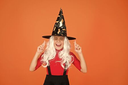 Hope spell works. Little child in witch costume. Halloween party. Small girl in black witch hat. Autumn holiday. Join celebration. Magical spell. Small witch with white hair. Wizard or magician Banque d'images