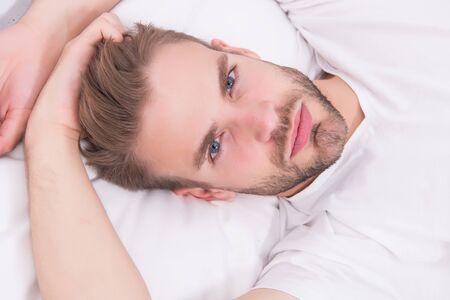 Practice calming activities such as meditation before going to bed. Healthy sleep concept. Tips promoting healthful sleep habits. Handsome man relaxing in bed. Establish regular nightly sleep pattern