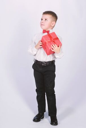 Shopping. Boxing day. New year. little boy with valentines day gift. Birthday party. tuxedo style. Happy childhood. happy child with present box. Christmas. happy retro guy go shopping