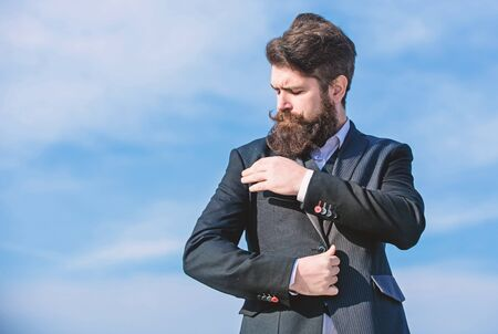 Just right. Man formal suit adjusting jacket. Male fashion formal menswear. Flawless outfit. Fashion trend. Guy beard and mustache wear formal clothes. Businessman bearded face sky background Stock Photo