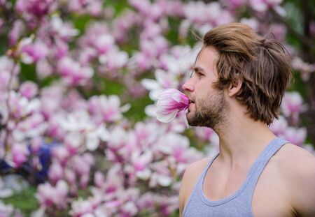 Spring beauty. Hairdo styling. Hair care and beauty. Unshaven man magnolia bloom. Beautiful hairstyle. Man flowers background defocused. Botany nature. Male beauty. Hipster enjoy blossom aroma