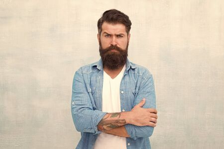 Barber salon. Male beauty concept. Well groomed macho. Brutal handsome hipster man on grey wall background. Bearded man trendy hipster style. Hipster with beard and mustache wear denim shirt