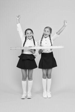 Geometry school lesson. Teamwork concept. Close or far. Measuring skills. Measuring distance. Measuring equipment. Kids students study math. Knowledge day. Schoolgirls school uniform hold big ruler