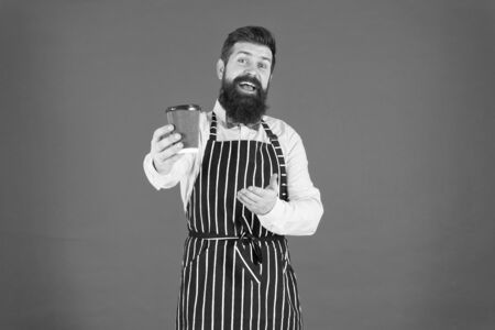 this is for you. bearded man hold take away coffee. brutal waiter in cafe. mature man red background. skilled servant. barista hipster chef apron. elegant confident bartender. male drink coffee Foto de archivo