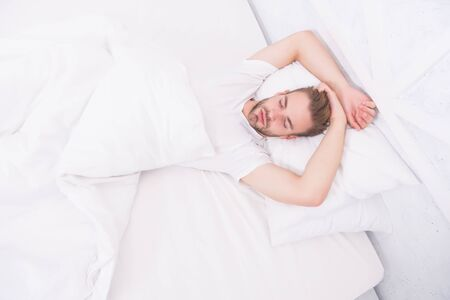Healthy sleep concept. Tips promoting healthful sleep habits. Handsome man relaxing in bed. Establish regular nightly sleep pattern. Practice calming activities such as meditation before going to bed