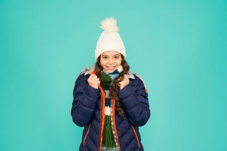 Feeling comfy. Cold season shopping. Child in padded warm coat. Seasonal fashion. Winter holidays. Fashion girl winter clothes. Fashion trend. Kid wear hat and jacket blue background. Winter sports Stock Photo
