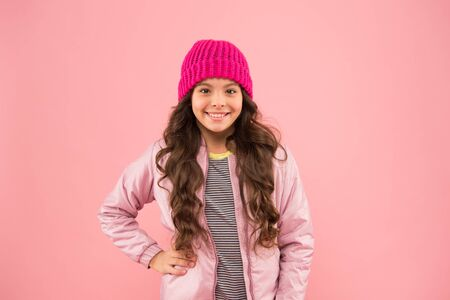 cheerful child in warm winter clothes. seasonal fashion for kids. small beauty pink wall. little girl puffer jacket and knitted hat. health care in cold weather. good mood any weather