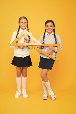 Move from theory to practice. Excellent pupils. Secondary school. Schoolgirls tidy appearance school uniform hold big rulers for geometry school lesson. Kids cute students study math. Knowledge day