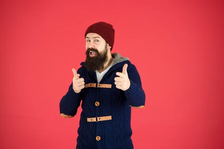 Winter menswear. Clothes design. Man bearded warm jumper and hat red background. Winter season menswear. Personal stylist. Warm and comfortable. Fashion menswear shop. Masculine clothes concept