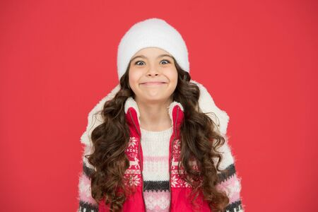 winter holidays began. winter activity for kids. happy childhood. cheerful child in knitted hat. feeling cosy in warm clothes. winter fashion. portrait of pure beauty. small girl long curly hair