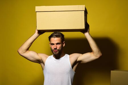 Guy with sexy torso holds box above head. Imagens