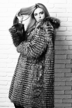 fashionable sexy woman in fur on brick wall studio background