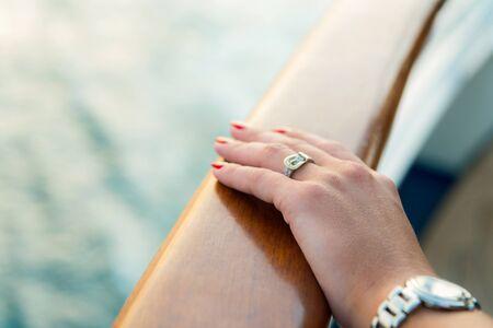 Lancette e orologio da polso femminili con manicure rosso e anello d'oro sul dito con diamanti vicino all'acqua