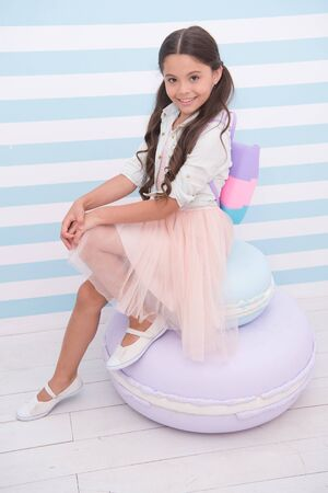 Born to be model. Child girl adorable smiling face posing on cute macaroon pouf. Kid long curly hair wear fashionable outfit. Girl with cute bag posing striped background. She likes to be model