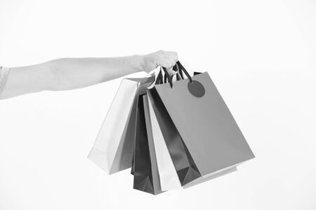Shopping bags in hand. Paper bags of different colors. Bags or paperbags isolated on white. Shopping during sale and black friday concept. Holidays preparation and celebration. Gift and present Stock Photo