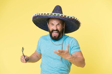 Hot tempered people. Man shouting face in sombrero hat yellow background. Guy with beard looks annoyed or angry in sombrero. Traditional rules of behaviour and manners. Man annoyed behaviour shout
