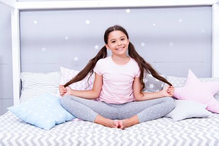 Relaxation and meditation. Girl child sit on bed in her bedroom. Kid prepare to go to bed. Pleasant time for evening meditation. Girl kid long hair cute pajamas relaxing and meditating in bedroom