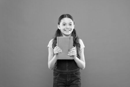 Childrens literature. happy little girl with notebook. literature lesson. school girl read book on orange background. poetry and novel. modern education. writing notes. kid diary. back to school