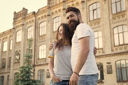 Happy together. Couple in love walking having fun. Tender hug. Couple relaxing enjoying each other. Hipster and pretty woman in love stand in street architecture building background. Feel my love