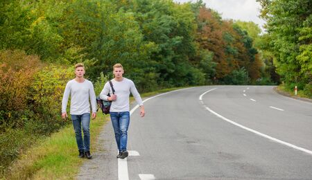 First and foremost. traveler hitchhiking on highway. on the way home. future. twins walking along road. two brothers go adventure. friendship. men hitch hiking. man casual style travel with backpack.