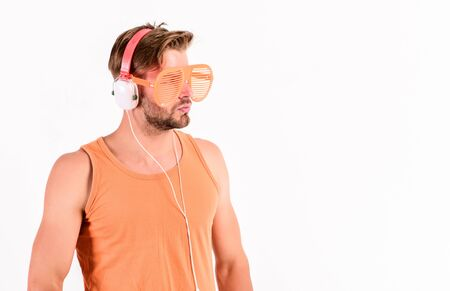 Guy unshaven face listening summer music. Dj boy. Technology and entertainment. Modern life. Handsome man with headphones and sunglasses. Party concept. Summer music chart. Popular summer track list. Zdjęcie Seryjne