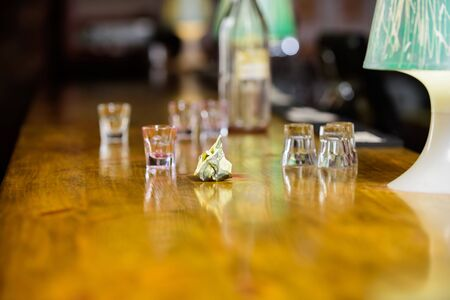 Cash payment. Ordering drinks in bar. Purchase and payment. Cash money concept. Leave tips for bartender. Tip given to waiter. Crumpled money cash at bar counter. Empty glasses and bottle on table.