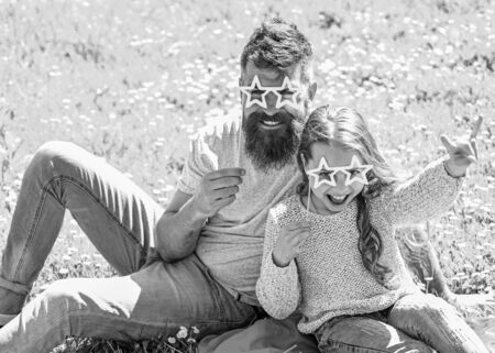 Father and daughter sits on grass at grassplot, green background. Superstar concept. Child and dad posing with star shaped eyeglases photo booth attribute at meadow. Family spend leisure outdoors.