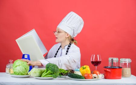 Female in hat and apron knows everything about culinary arts. Improve cooking skill. Culinary expert. Woman chef cooking healthy food. Girl read book best culinary recipes. Culinary education concept