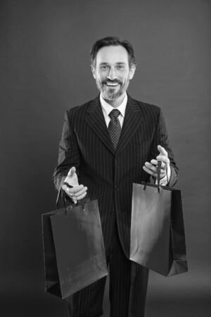 I help economy, I shop a lot. Happy shopper red background. Businessman hold shopping bags. Mature man enjoy shopping. Blowout sale. Shopping gifts. Black Friday. Good day for shopping