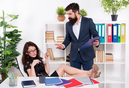 sexy lady relax at table on workplace. glamour office life. ceo man angry on naughty girl. business relations. business partners couple work together. you cant handle the job. where is my report Stock Photo