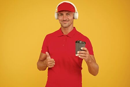 Man recommend to try drink. Hot beverage. Here is your coffee. Cafe operator cashier hold coffee cup. Have a nice day. Coffee to go. Cafe stuff red uniform with cap serving coffee yellow background