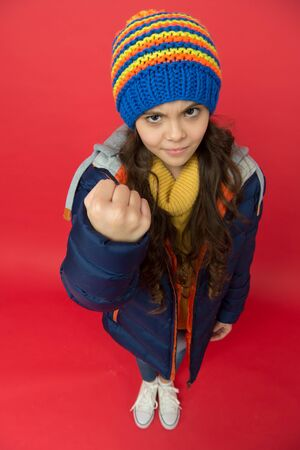Punch in face. Threatening fist. Little girl wear winter clothes red background. Childhood concept. Emotional girl long hair knitted hat. Teen girl casual style. Emotions mood. Bullying prevention