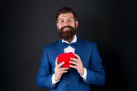 Bearded man groom in formal suit. Health care. Heart in hands. Best wishes from sincere heart. Businessman in bow tie. Heart symbol aesthetics. Valentines day holiday. Love and relations. Wedding day Standard-Bild
