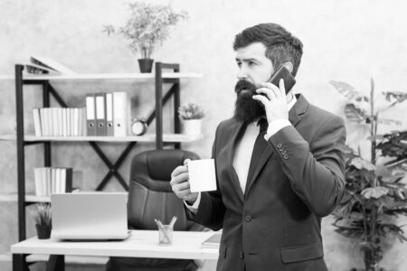 Man bearded businessman hold cup and smartphone. Coffee is pledge of successful negotiations. Caffeine addicted. Mobile call. Start day with coffee. Coffee relaxing break. Boss enjoying energy drink