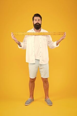 Bearded and moustached. Bearded man measuring beard hair on yellow background. Bearded maths teacher or student with metric ruler. Brutal caucasian guy being proud of hair growth on bearded face