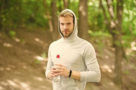 Stay hydrated. Athlete drink water after training in park. Vitamins and minerals. Man athletic sportsman hold bottle water. Man athlete sport clothes care about water balance. Healthy lifestyle