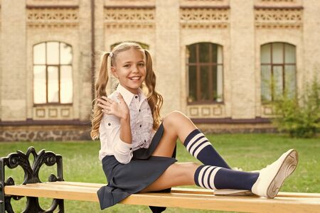 Time to relax and have fun. Relaxing in school yard. Perfect schoolgirl relaxing between classes. Life balance. Student adorable child in formal uniform relaxing outdoors. Pleasant minutes of rest