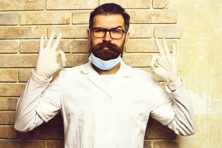 Bearded brutal caucasian doctor or postgraduate student in gloves
