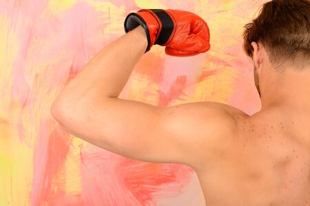 Guy shows naked muscles wearing red leather boxing glove. Man turned back to colorful background. Boxer with strong biceps against pink, orange and yellow wall. Sports and strength concept