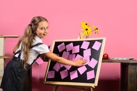 Schoolgirl with happy face puts sticky notes on board.