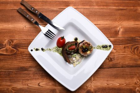 Grilled steak slice, rolled on salad near grilled garlic on white plate, top view. Dish with sophisticated presentation on wooden background Stock Photo