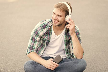 favorite song. student relax use phone. guy chatting outdoor. man sit on ground. carefree student in headset. free time. online education. listen music. ebook concept. man checkered shirt Stock fotó
