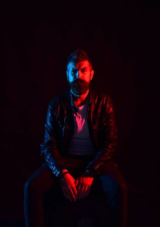 Macho in black leather jacket in blue and red light. Man with beard isolated on black background. Guy with thoughtful face and brutal look sits on chair. Brutality, masculinity and confidence concept.