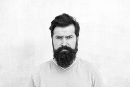 Strenges Gesicht. Wahrnehmungen von männlicher Schönheit auf der ganzen Welt. Mann bärtiger Hipster stilvoller Bart grauer Hintergrund. Stilvolle Bart- und Schnurrbartpflege. Hipster-Auftritt. Bartmode und Friseurkonzept Standard-Bild