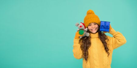 Shopping tips. Rat symbol of year. Happy girl hold mouse toy and wrapped gift box. Kid knitted sweater and hat play plush toy. Shop for kids. Happy 2020 year. Gift for good luck. Appease with gift Stock Photo