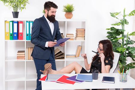 boss and employee. female domination. male against female. business couple in work office. confident businesswoman relax while man assistant working. businessman give instructions to lazy secretary
